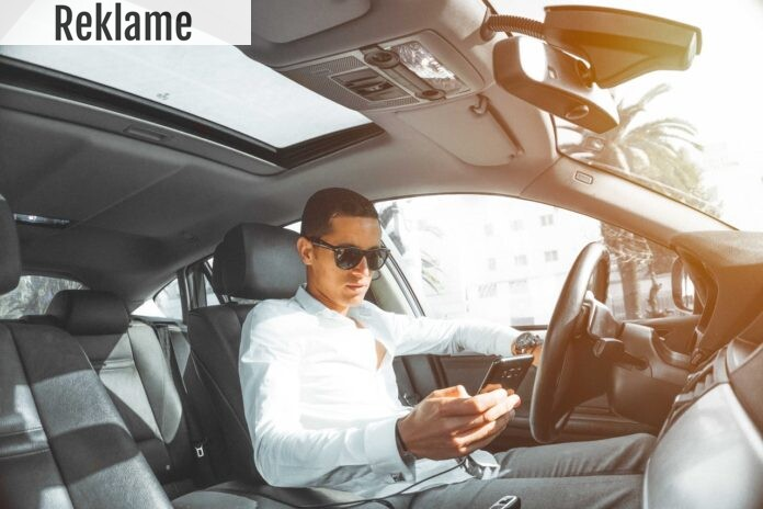 En tjekker sin mobiltelefon i sin parkerede bil